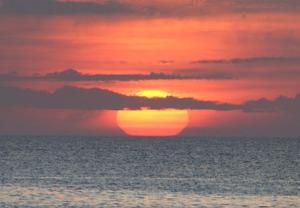 sun rising at ocean's  horizon